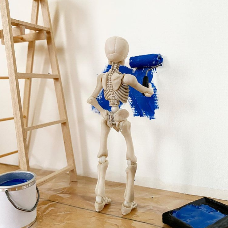 skelly figure painting a wall