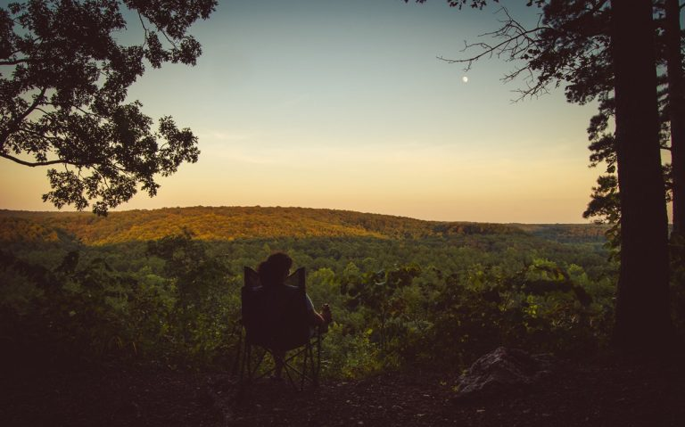 woman outdoors in chair, overlooking peaceful valley